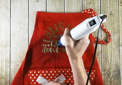 Make this cute heat embossed Apron for Christmas with this easy to follow tutorial. With a few tools and your Silhouette or Cricut machine, you'll be able to create this heat embossed Apron. This DIY project is easy and quick to make and is the perfect decoration for home. #ChristmasSilhouette #ChristmasCricut #ChristmasSVG